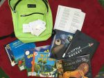Photo of backpacks, laminated constellation cards, and picture books about camping